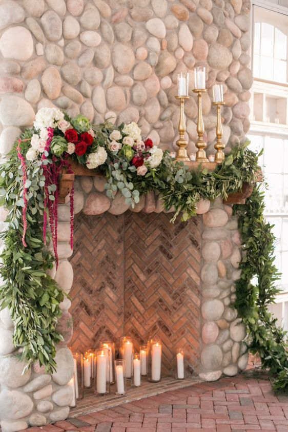 a large fake fireplace deocrated with lush greenery, white and burgundy blooms and with candles on the mantel is a very chic and refined idea