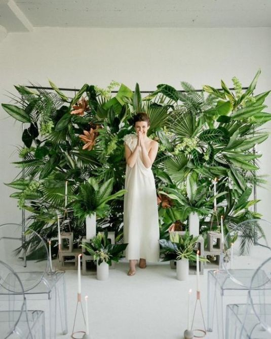 a living wall backdrop of large tropical leaves and a concrete stand with leaf arrangements in vases to bring outdoors indoors