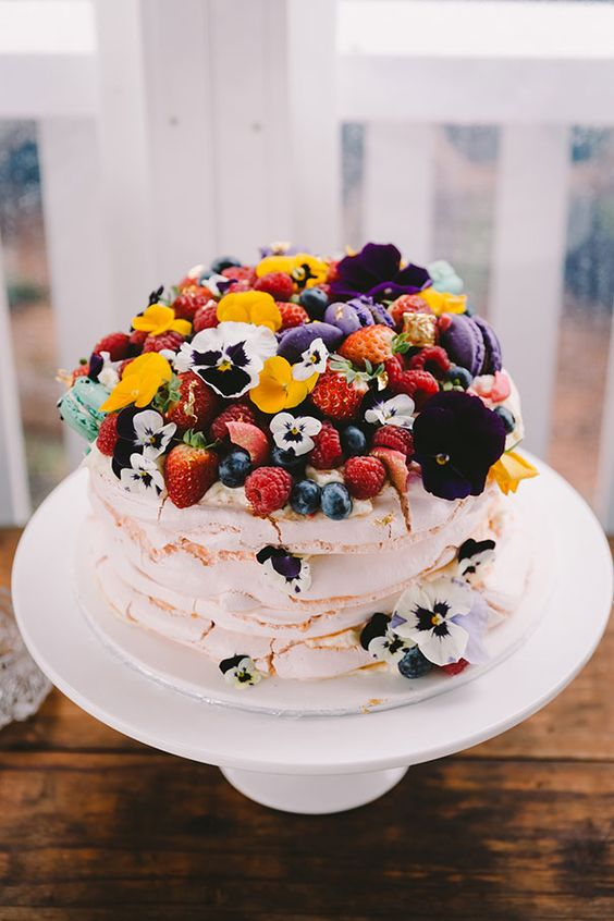 a lovely and bright pavlova wedding cake with berries, fruits and colorful edible blooms is a splash of colors and gorgeousness
