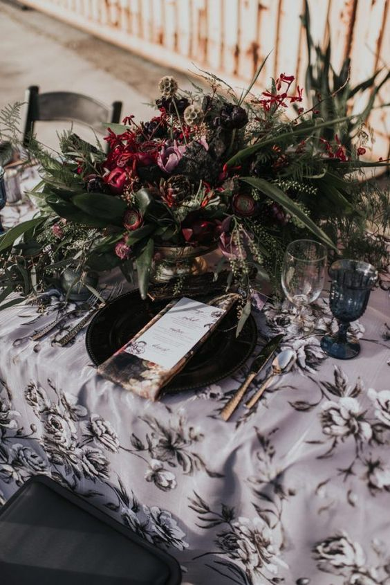 a lush dark floral centerpiece with textural greenery, black and deep red blooms for a statement