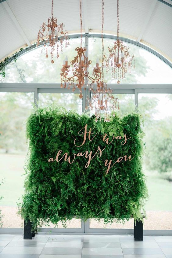 a lush greenery wall with a quote in copper letters and refiend copper chandeliers over the wall is a cool way to feel outdoors while being indoors