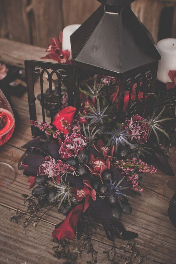 a luxurious decadent dark centerpiece of a black lantern with thistles, deep red and purple blooms and grapes