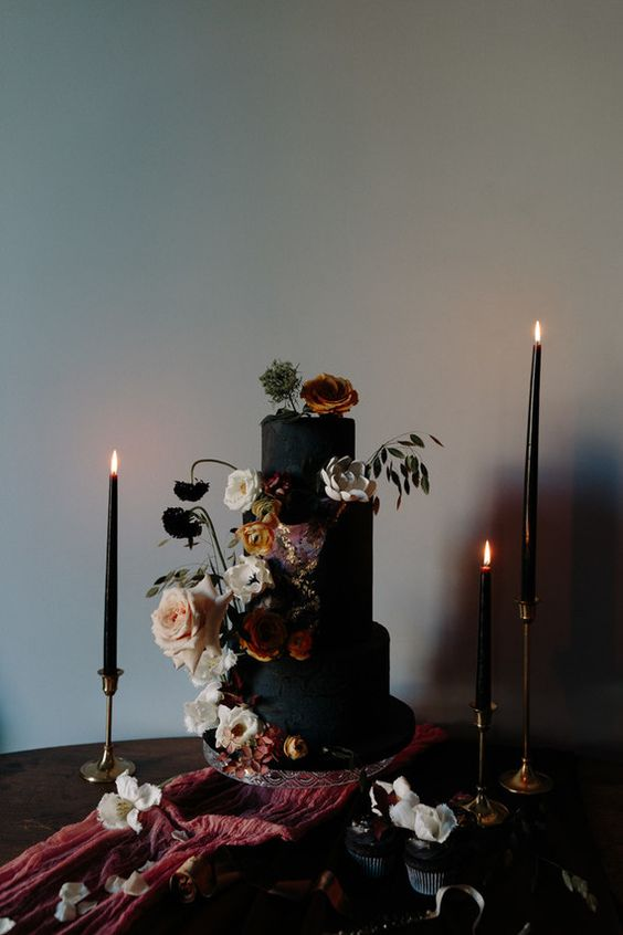 a matte black textural wedding cake with lush moody blooms for decor