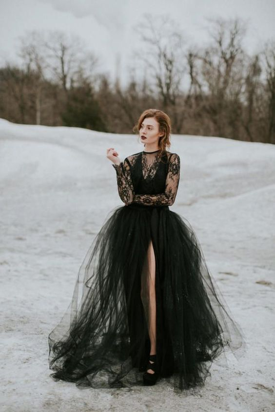 a modern black wedding dress with a lace top, a tulle skirt with a front slit and long sleeves, black shoes and a moody lipstick