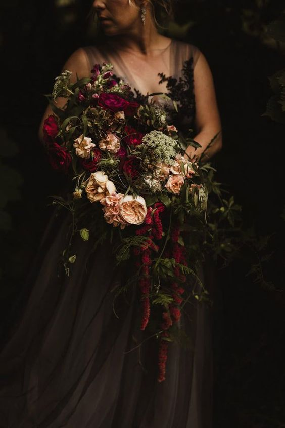 a moody Halloween wedding bouquet with burgundy and blush blooms, lots of greenery and cascading foliage