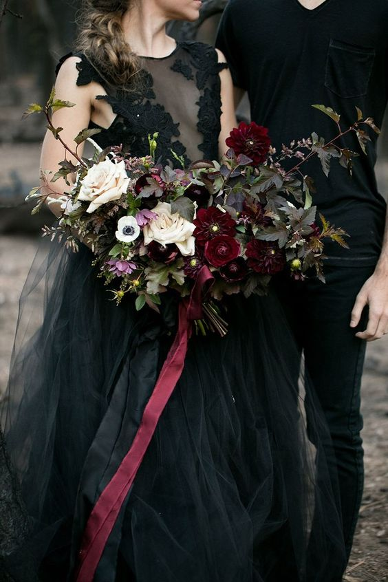 a moody Halloween wedding bouquet with burgundy blooms, neutral ones, greenery and grasses is chic