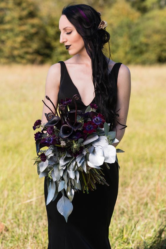 a moody Halloween wedding bouquet with deep purple, burgundy blooms, silver goliage and lotus is a jaw-dropping piece
