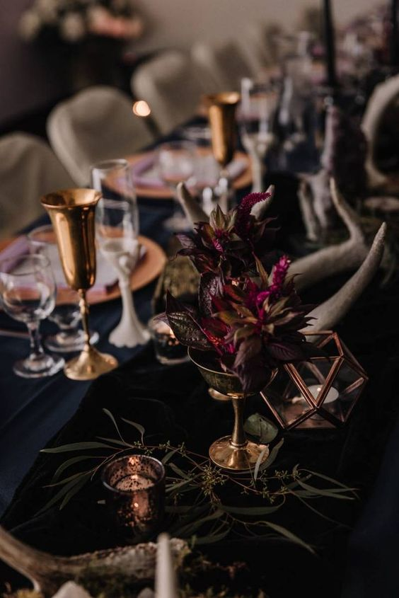 a moody Halloween wedding centerpiecce of fuchsia blooms, greenery, candles and antlers is a stylish idea to go for