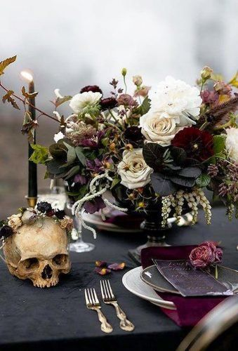 a moody and refined Halloween wedding centerpiec eof neutral and burgundy blooms, greenery and dark foliage, black candles and skulls