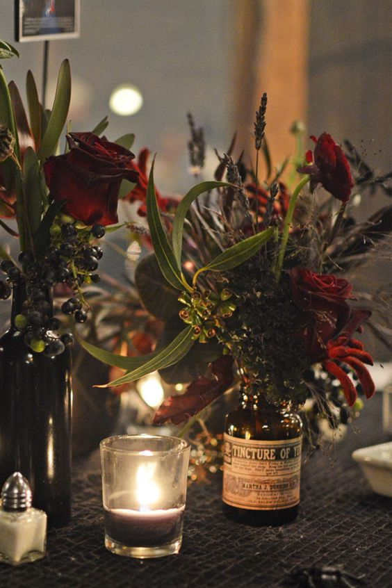 a moody cluster Halloween wedding centerpiece of burgundy roses, greenery and berries plus a dark candle in a glass