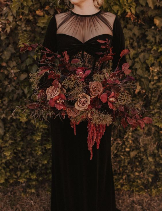 a moody wedding bouquet of dusty pink, burgundy and pink blooms, dark foliage, moss and greenery for Halloween
