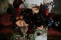 a moody wedding bouquet with burgundy, red, black and peachy blooms, touches of blue, berries, leaves and blue ribbons