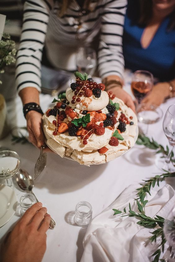 a pavlova wedding cake topped with fresh berries, mint and some dip is a very tasty idea to enjoy