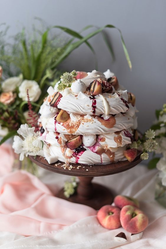 a pavlova wedding cake with berry compote, fresh peaches, nuts, blooms and meringues on top is amazing for a fall or summer wedding