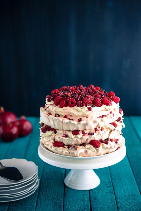 a pretty pavlova wedding cake with fresh raspberries and pomegranate seeds is a delicious wedding cake alternative