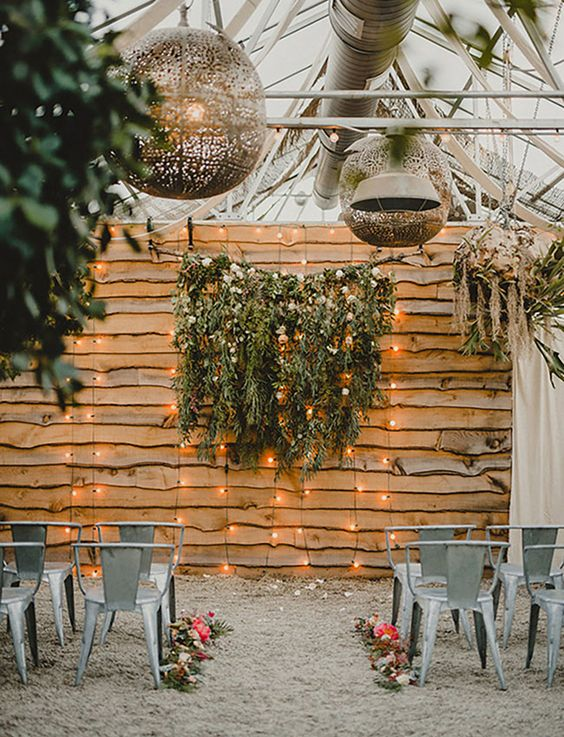a reclaimed wood wall, greenery and blooms and lights hanging down to create a cozy and intimate wedding ceremony space