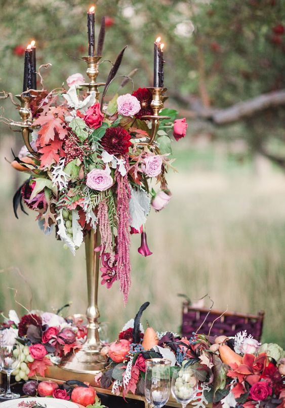a refined and moody Halloween wedding centerpiece of a tall candlelabra with black candles, pink and burgundy blooms and greenery