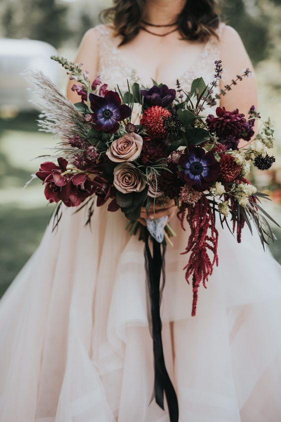 a refined moody wedding bouquet with pink purple, dusty pink, blue, red flowers, greenery and grasses is very chic