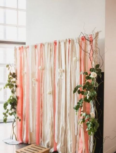 a romantic wedding backdrop of white and pink ribbons, greenery and white roses attached to the ribbons looks very cool