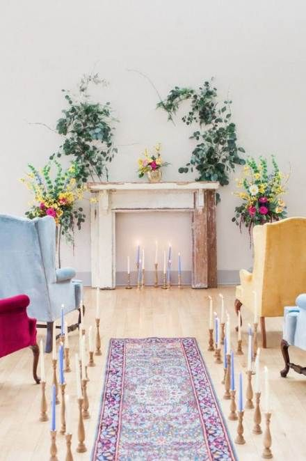 a shabby chic mantel with colroful candles, greenery and floral arrangements and colorful vintage chairs