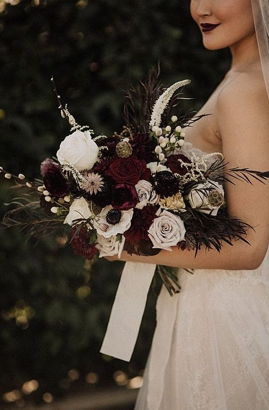 a sophisticated Halloween wedding bouquet with burgundy, white blooms, grasses, berries and some foliage