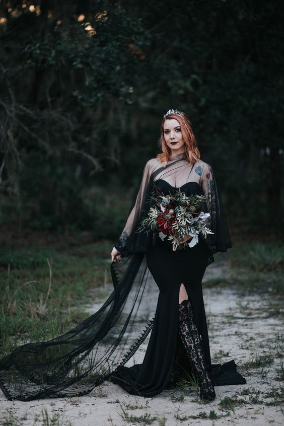 a statement Halloween bridal look with a strapless black mermaid wedding dress with a front slit and a sheer tulle coverup