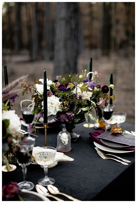 a stunning Halloween wedding centerpiece of white, purple and deep burgundy blooms and greenery plus thin and tall candles