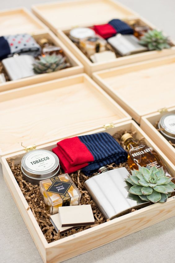 a stylish groomsmen box with socks, a succulent, a flask, a mini alcohol bottle, some snacks, tobacco and matches