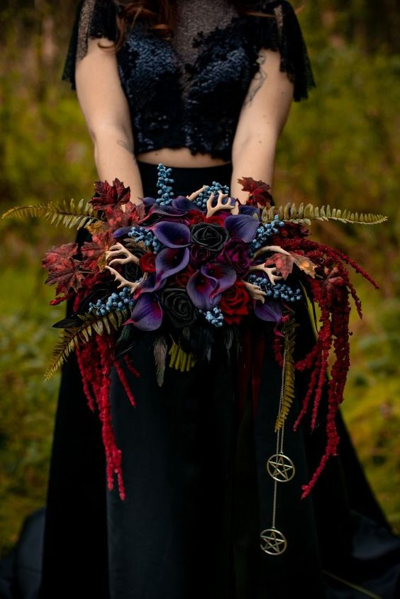 a super bold Halloween wedding bouquet with burgundy, blue and deep purple blooms, red cascading ones, ferns and mini antlers