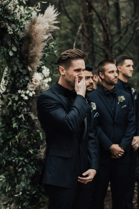 a total black look for the groom with a three-piece suit, a bow tie and the groomsmen wearing the same