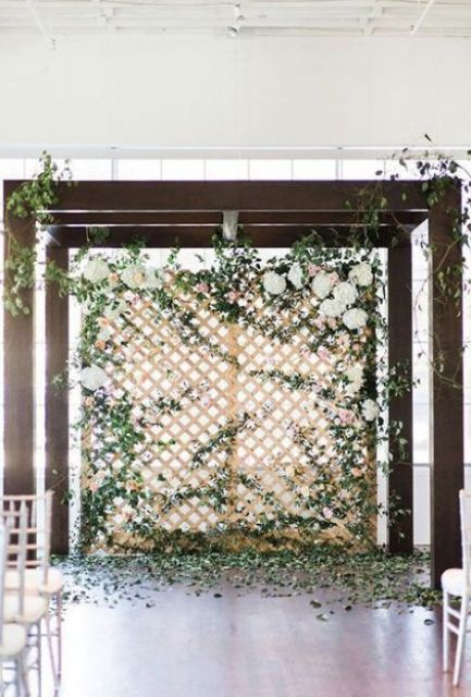 a trellis wall with lots of greenery, white hydrangeas and much foliage on the floor is very fresh and romantic