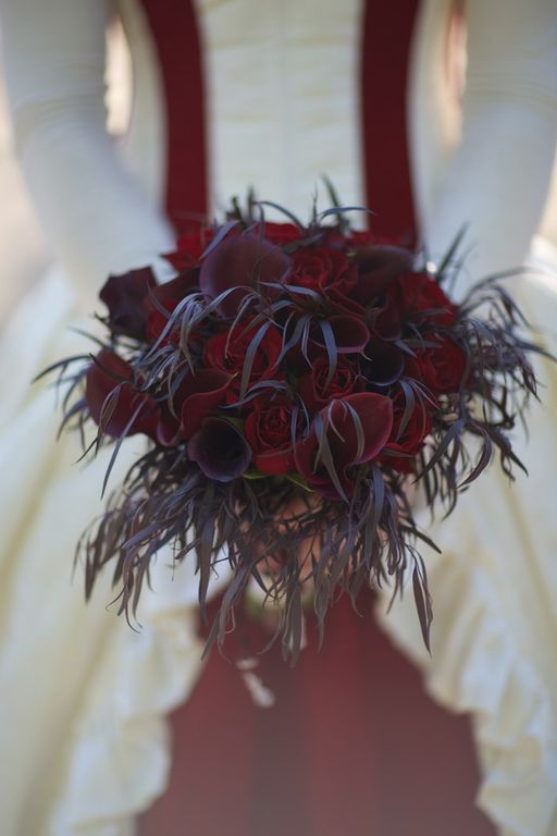 a unique Halloween wedding bouquet with red and burgundy callas and roses and foliage