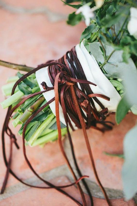 a white ribbon and lots of leather laces for a boho wedding bouquet