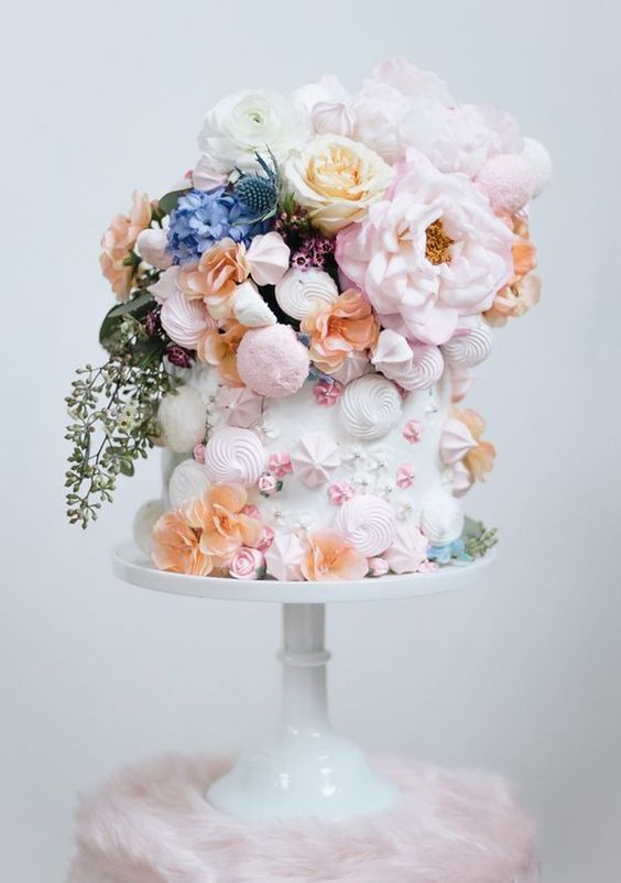 a white wedding cake decorated with pink and white meringue kisses, stars and roses and lots of beautiful pastel blooms