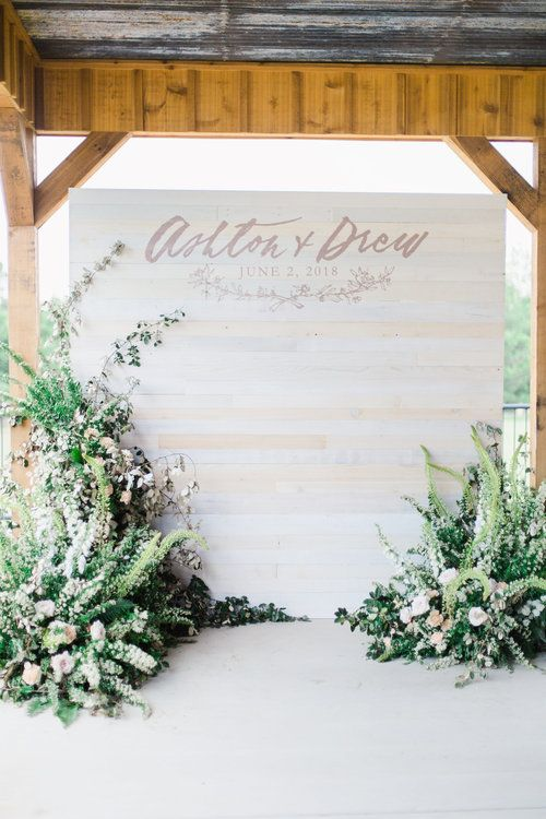 a whitewashed wooden wall with letters and monograms and greenery and bloom arrangements around