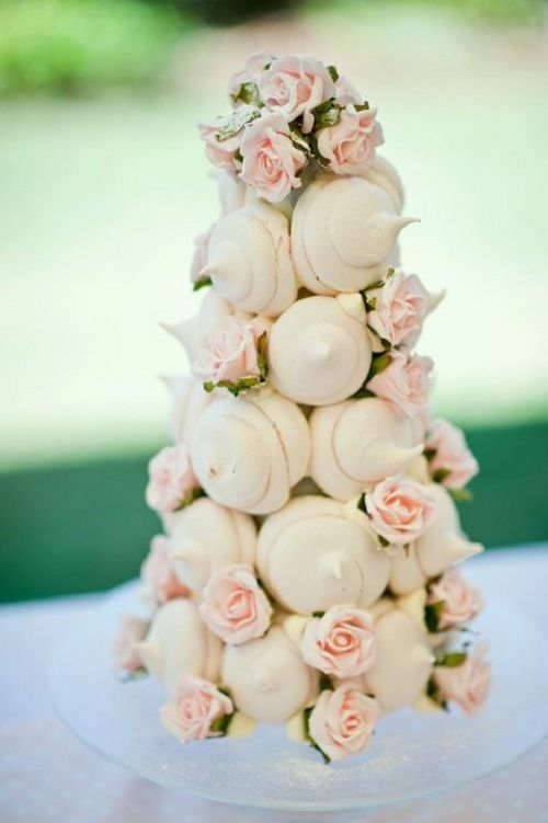 an alternative wedding cake made of meringue kisses and blush blooms is a lovely wedding dessert idea to rock