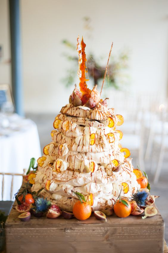 an amazing pavlova wedding cake with citrus slices and fresh fruits plus some caramel on top for a fall wedding