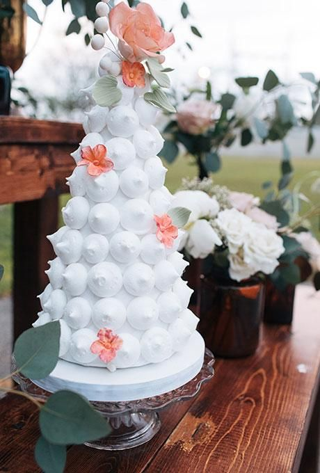 an elegant meringue wedding cake decorated with pink sugar blooms and leaves is a chic and lovely idea