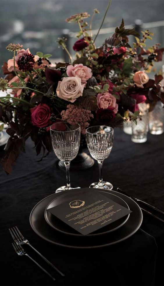 an exquisite moody Halloween wedding centerpiece of fuchsia, blush and depe purple blooms, greenery and grass is wow