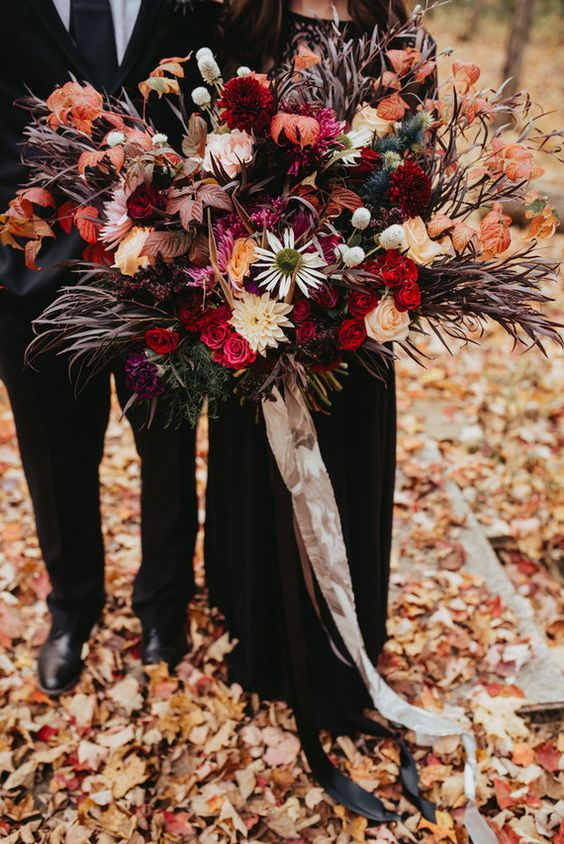 an oversized colorful wedding bouquet with red, pink, purple, peachy, orange blooms, dark foliage and greenery to stand out with a black wedding dress