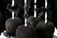 apples covered with black and on sticks with glitter spiders are lovely and chic Halloween favors
