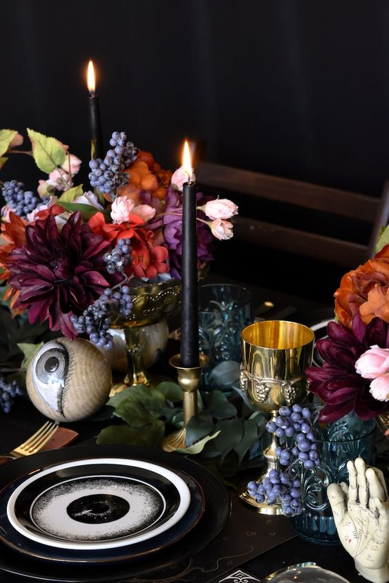 bold and catchy wedding centerpiece of colorful blooms, berries, black candles and larrge eyeballs are scary yet stylish