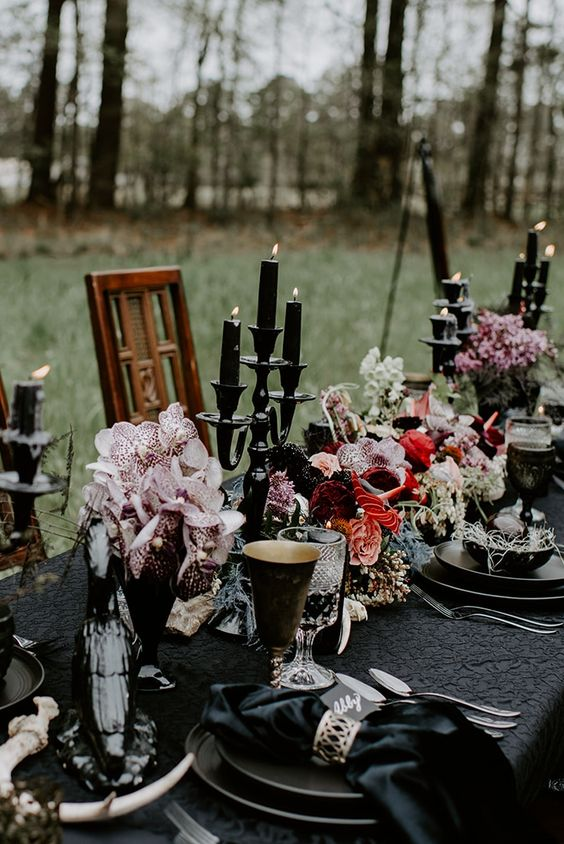 bold and chic Halloween wedding centerpiece of pink and red blooms, blush orchids, black candles in tall candleholders are amazing
