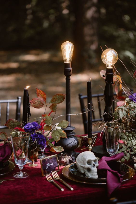 super bold purple blooms, greenery, black candles and bulbs on stands make up a fantastic Halloween wedding centerpiece