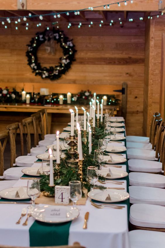 a Christmas tablescape with an evergreen runner, candles in gold candleholders, gold cutlery and emerald napkins