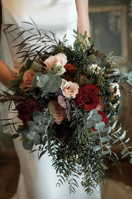 a Christmas wedding bouquet of greenery, eucalyptus, blush and burgundy blooms and privet berries is very chic