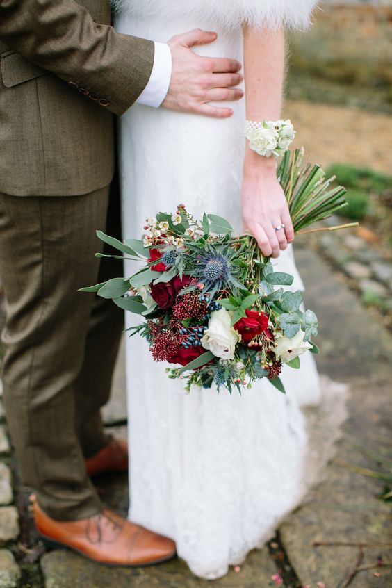 a Christmas wedding bouquet of white and burgundy blooms, thistles, berries and greenery is a chic idea