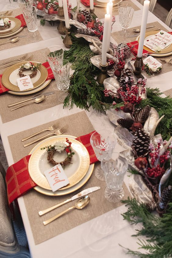 a Christmas wedding table setting with an evergreen, pinecone and berry runner, thin candles, red napkins and mini wreaths for place settings