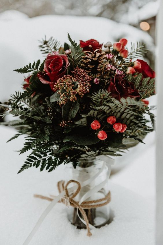 a beautiful Christmas wedding bouquet of greenery, red roses, berries and pinecones is a very cool option