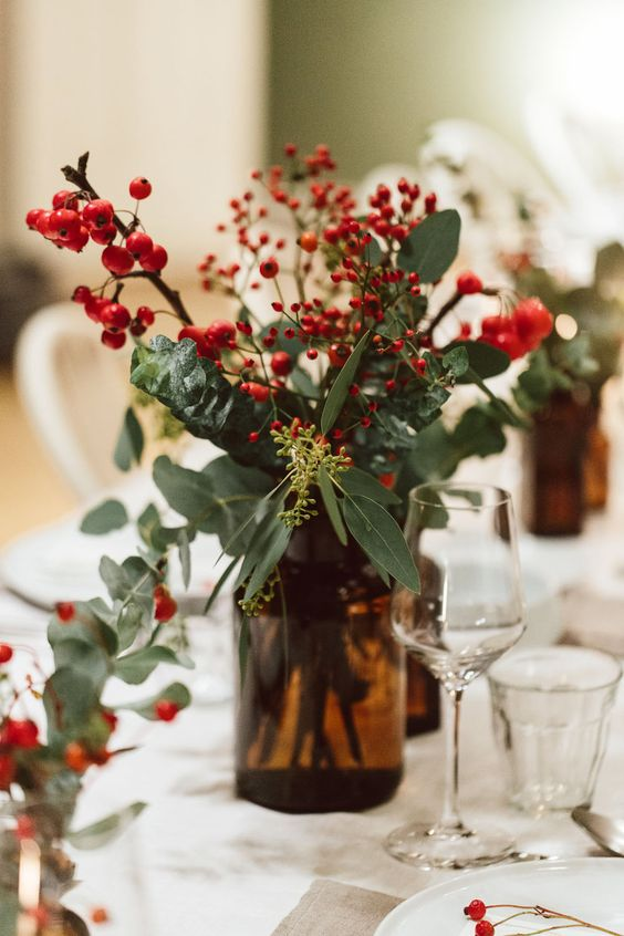a beautiful Christmas wedding centerpiece of an apothecary bottle, greenery, berries looks very festive and cozy
